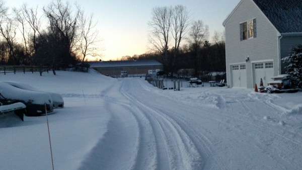 View of partially plowed driveway towards indoor